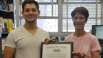 Javier Castro and Diane Mitchell hold research paper award