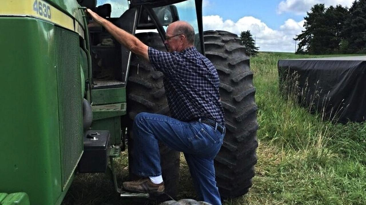 Farmer getting into tractor