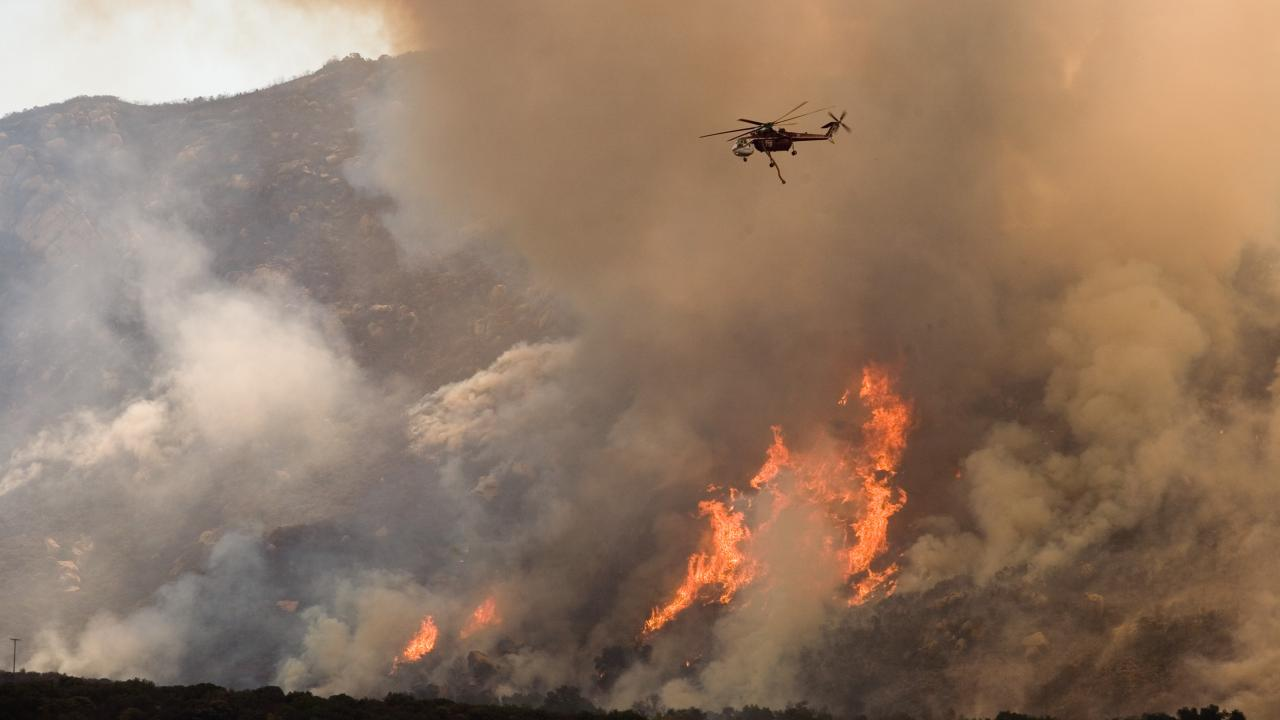 A helicopter drops water on California wildfire