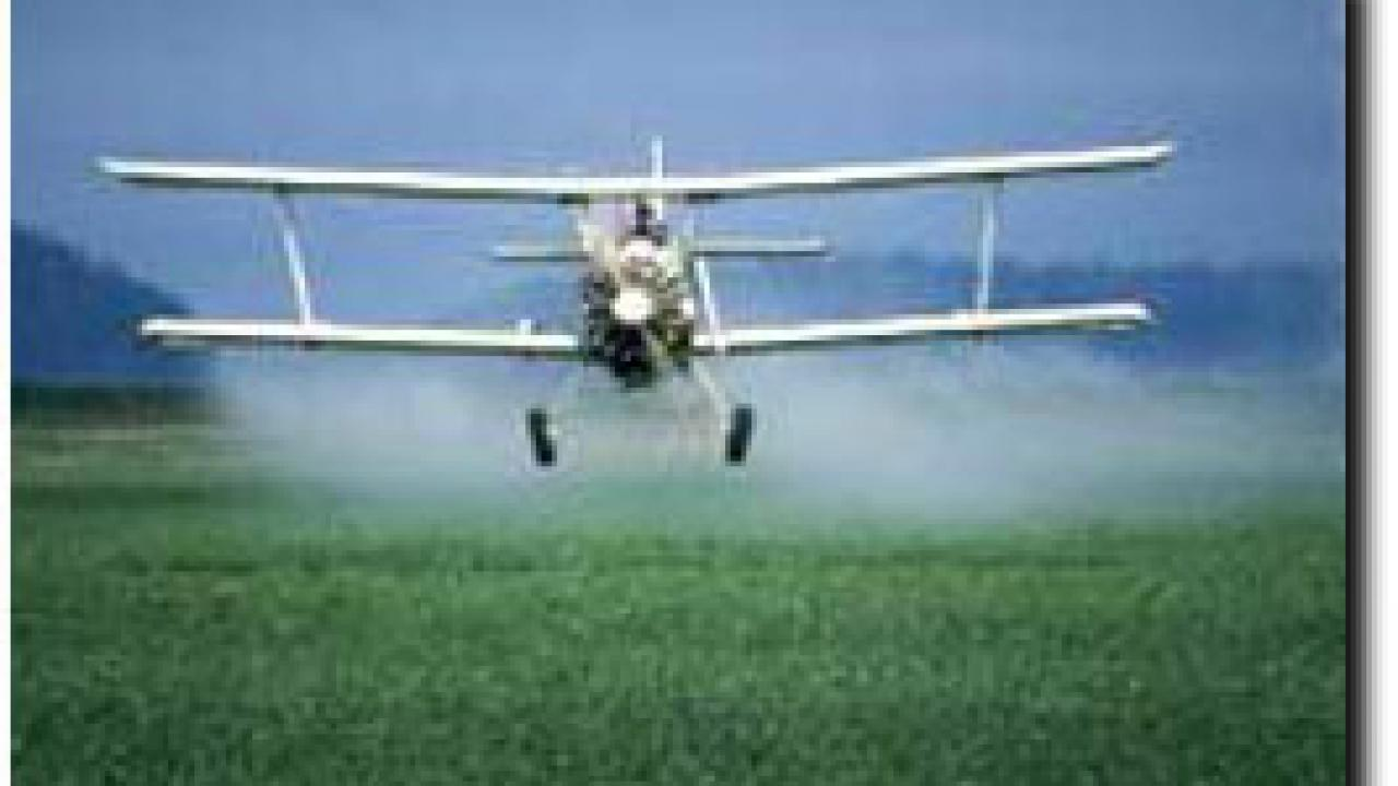 Crop duster spraying agricultural fields with pesticide