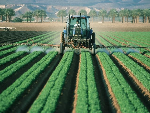 Tractor sprays pesticides on field